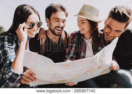Group Of Young Smiling People Holding Paper Map. Casualy Dressed Happy Travelers With Backpacks Plan