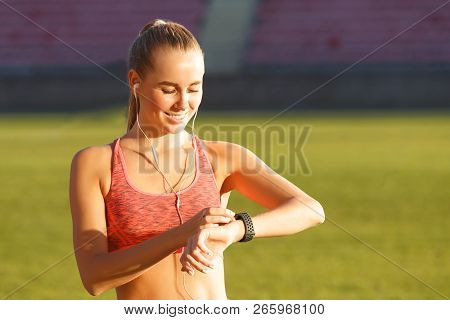 Positive Athletic Attractive Blonde Long Haired Woman In Sportswear Standing At The Football Stadium