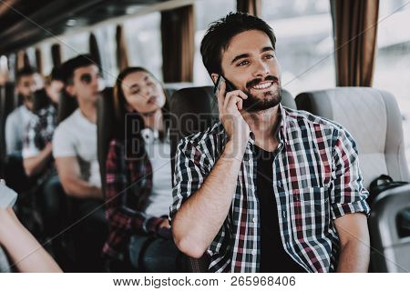 Young Smiling Man Talking On Phone In Tourist Bus. Young Handsome Man Sitting On Passenger Seat Of T