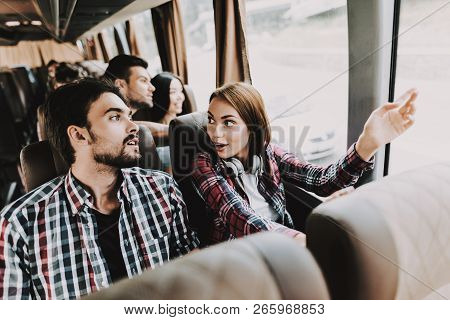 Young Smiling Couple Traveling On Tourist Bus. Handsome Man And Beautiful Woman Relaxing On Passenge