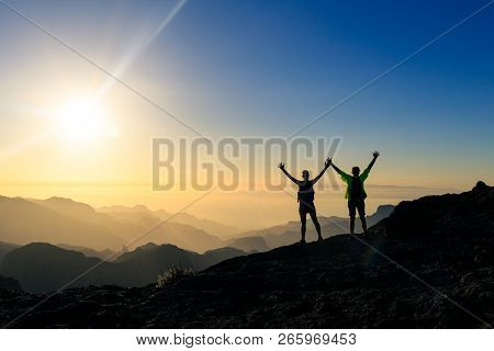 Couple Hikers Success And Trust In Mountains, Accomplish With Arms Up Outstretched. Young Man And Wo