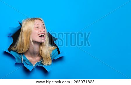 Happy Blonde Girl Looking Through Hole In Paper. Woman Breaking Through Paper Wall. Emotions. Emotio