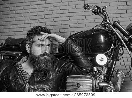 Bikers Lifestyle Concept. Man With Beard, Biker In Leather Jacket Near Motor Bike In Garage, Brick W