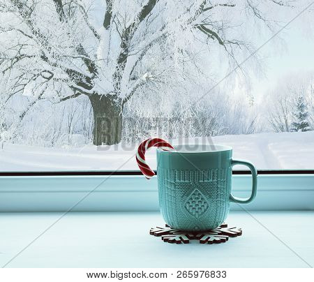 Winter still life - cup with candy cane on windowsill and winter forest landscape outside. Cozy winter still life with concept of spending winter time indoors. Winter composition
