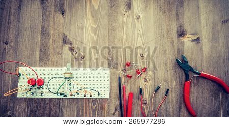 Workplace With Tools: Breadboard, Push Button, Resistors, Tweezers, Nippers, Soldering Iron, Wires, Microcircuit, Lamp Socket. Electronics Repair Service. Concept of Electronics, Programming. poster