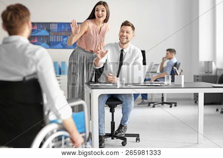 Young man in wheelchair with colleagues at workplace