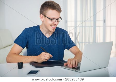 Man Working With A Graphics Tablet Behind A Laptop. Happy Man Working Sitting At The Table Surrounde