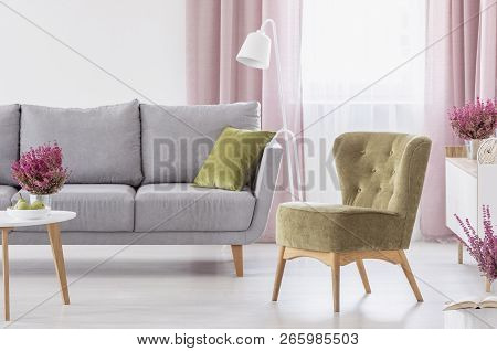 Green Armchair Standing In White Living Room Interior With Grey Couch, Window With Pastel Pink Drape