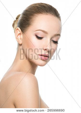 Beautiful face of young caucasian woman with perfect health fresh skin  - isolated on white.  Skin care concept. Female loooks down