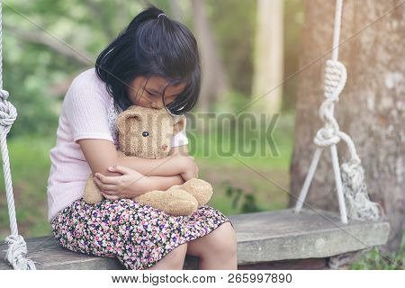 Sad Child Hugging Teddy Bear On Wooden Swing In Park.asian Little Girl Sitting With Best Friends For