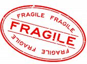 Grunge red fragile word oval rubber seal stamp on white background poster