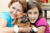 Latin grandmother and granddaughter hugging the family dog poster