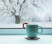 Winter still life - cup with candy cane on windowsill and winter forest landscape outside. Cozy winter still life with concept of spending winter time indoors. Winter composition poster