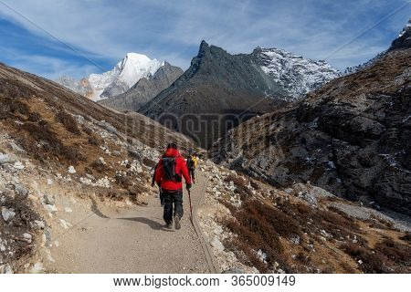 The Traveler Walking To The Snow Mountain Range Of Yading Nature Reserve Of China.