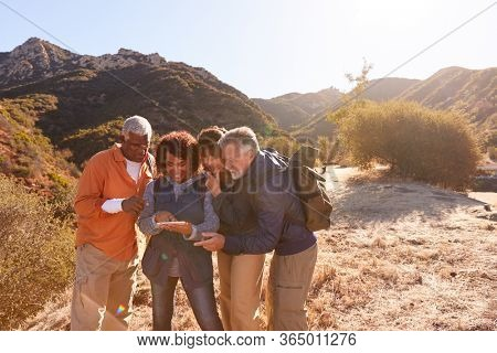 Group Of Senior Friends Checking GPS On Mobile Phone As They Hike Along Trail In Countryside