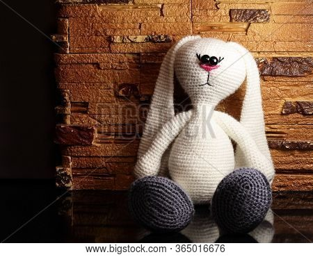 A White Toy Bunny Against A Stone Wall. The Bunny Is Tied With His Own Hands.