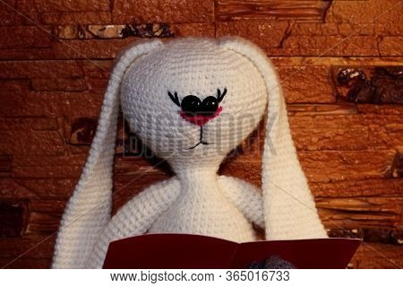 White Rabbit. White Stuffed Toy. Knitted Toy With Your Own Hands. Rabbit Reads A Book.
