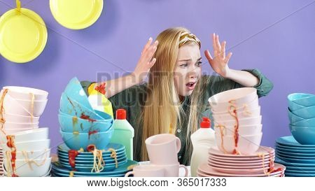 Young Woman In A Panic, Terrified Of The Number Of Unwashed Dirty Plates And Cups.