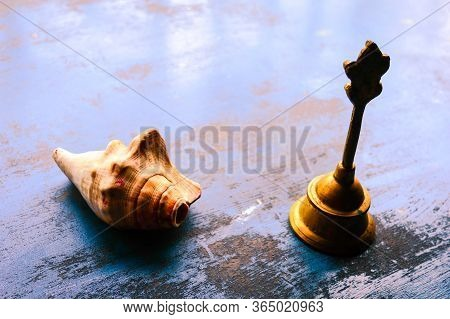 Close Up Still Life Of Antique Conch Shell And A Bell On Rustic Floor. Faith, Tradition, Spiritualit