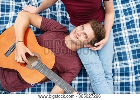Happy Couple In Love On A Romantic Date At The Park On A Picnic. Playing On A Guitar And Having Fun