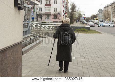 A Disabled Lonely Old Woman In A Coat Walking With A Cane Along A Deserted Street, Looking For Somet
