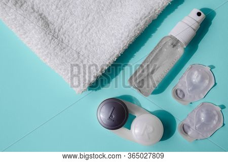 A Set For Using Contact Lenses. On A Blue Table Are Hand Sanitizer, Lens Blisters, A Lens Container,