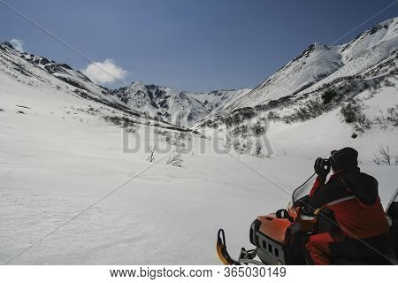 A Hunter On A Snowmobile Examines The Mountain Slope With Binoculars. A Man In A Red Jumpsuit Inspec