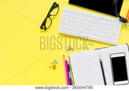 Online Education Concept. Tablet, Phone, Headphones, Notebook, School Supplies On Yellow Background.