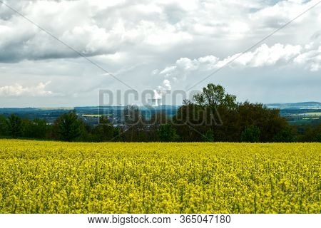 Nuclear Power Plant Behind An Oilseed Rape Field. Production Of Clean Electricity.