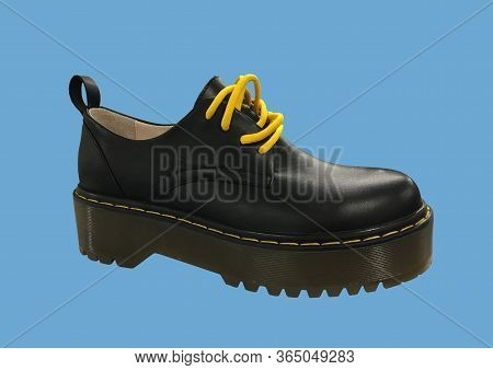 Black Leather Platform Shoes Isolated On Blue Background. Classic Shoes On A High Black Tractor Plat