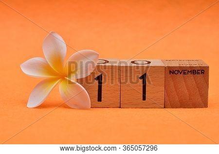11 November On Wooden Blocks With A Frangipani Flower On An Orange Background