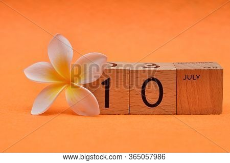 10 July On Wooden Blocks With A Frangipani Flower On An Orange Background