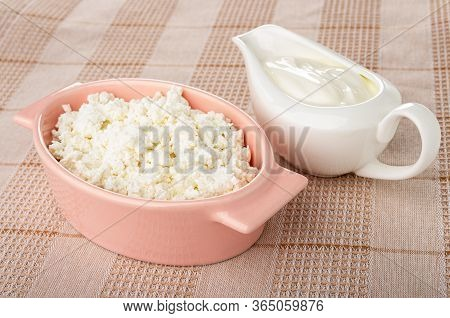 Defatted Grained Cottage Cheese In Pink Glass Bowl, Sauceboat With Sour Cream On Checkered Napkin On