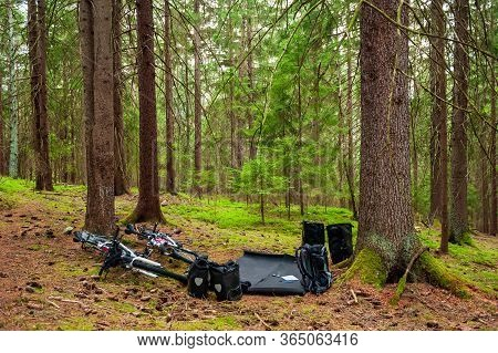 Two White Bikes Of Cyclists Lying On The Needles Floor In Coniferous Forest With All Equipment. Bike