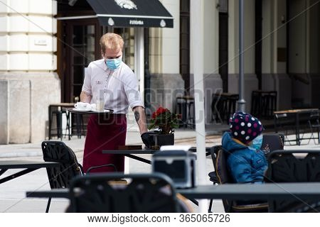 Vilnius, Lithuania - April 30 2020: Waiter With A Mask Disinfects The Table Of An Outdoor Bar, Café