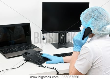 A Doctor In A Mask And Gloves Works On A Computer In A Polyclinic, A Hospital In An Emergency Room.d