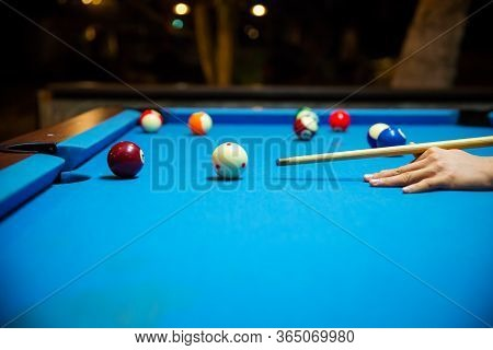 Pool Balls On The Blue Felt Pool Table With Player Hands And Pool Cue Stick. Indoor Sports. Sport An