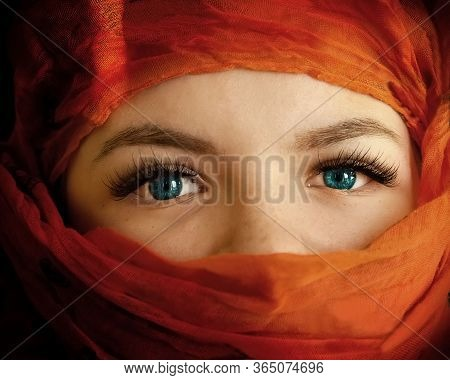Beautiful Eyes Of A Girl Close-up. The Head And Lips Are Covered With An Orange Cloth, A Veil. The G