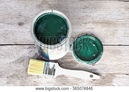 Can Of Green Paint A Brush On A Wooden Background. Tools For Painting. Open Jar Of Green Paint. Tin