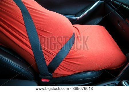 Close Up Pregnant Woman's Belly And Safety Belt In The Car. How To Correct Belt To Use Seat Belt For