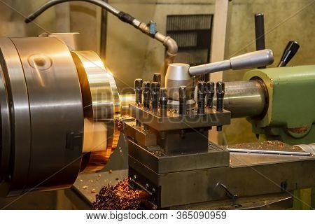 The Operation Of Lathe Machine Cutting The Brass Plate Parts With The Cutting Tools. The Metalworkin