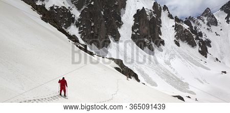 Snowy Mountains With Avalanche Traces, Sunlit Cloudy Sky, Hiker In Red With Ski Poles And Dog On Sno