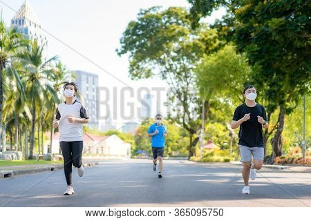 Asian Young Three Woman And Man Are Jogging And Exciseing Outdoor In City Park And Wearing Protectiv