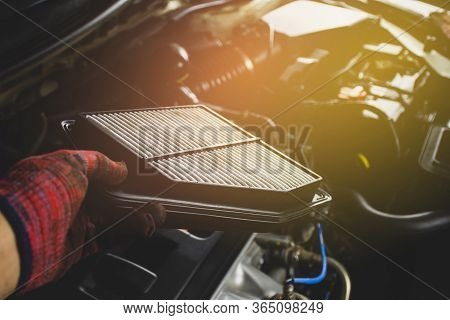 Car Air Filter In A Hand Of Mechanic Man Is Installing Into Air Filter Socket Of Car Engine,automoti
