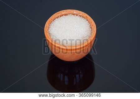 Spa Chemicals Ph Decreaser In A Small Orange Cup Isolated On A Glossy Black Background.  Used In Poo