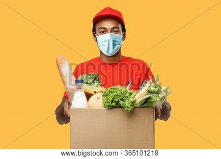 Delivery Concept - Handsome African American Delivery Man With Mask Carrying Package Box Of Grocery