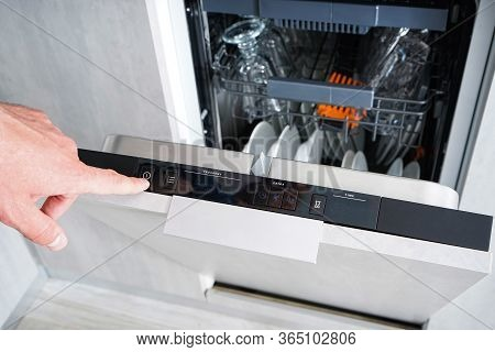 A Man Turn On And Off The Dishwasher. The Man Puts Dirty Dishes In The Dishwasher. Washing Dishes In