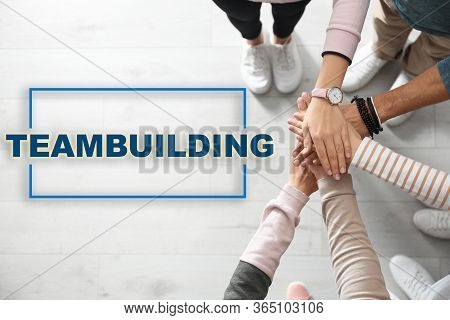 People Holding Hands Together Over Wooden Background, Closeup. Teambuilding Concept