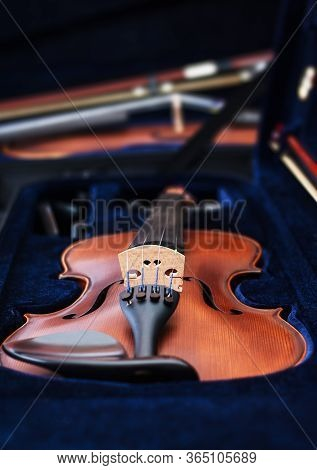 Viewing Down The Length Of A Violin Resting In The Soft Blue Interior Of Its Case With A Second Viol
