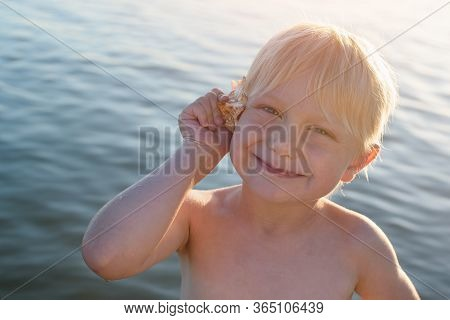Cute Fair-haired Boy Holding Seashell To His Ear. Sea Background..